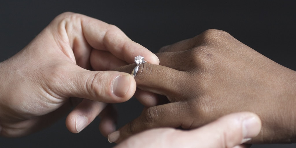 Man putting an engagement ring on a woman's finger