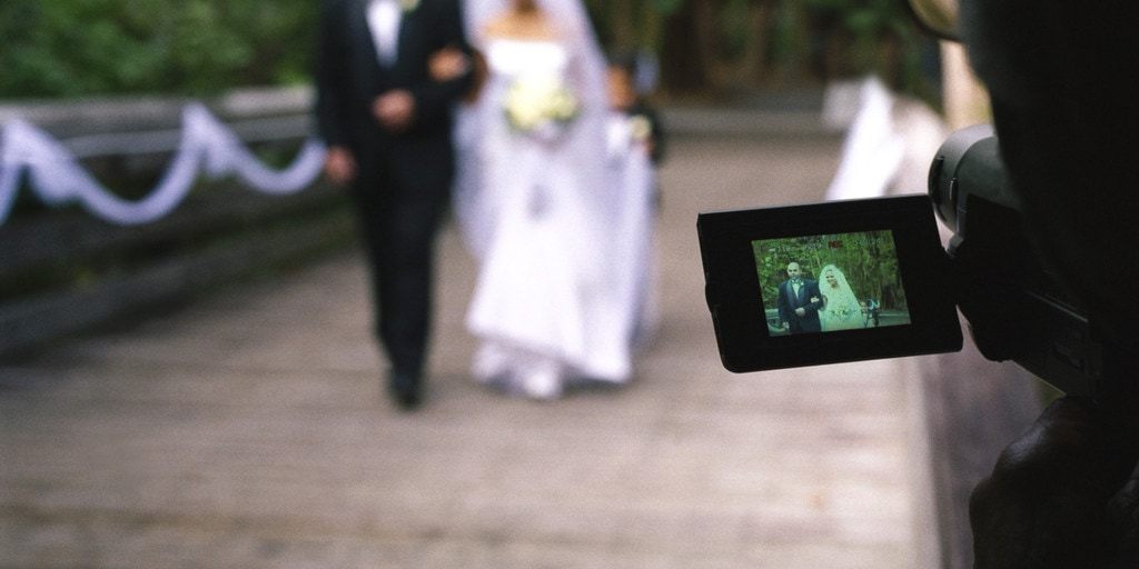 Video camera recording bride and father of the bride walking down aisle