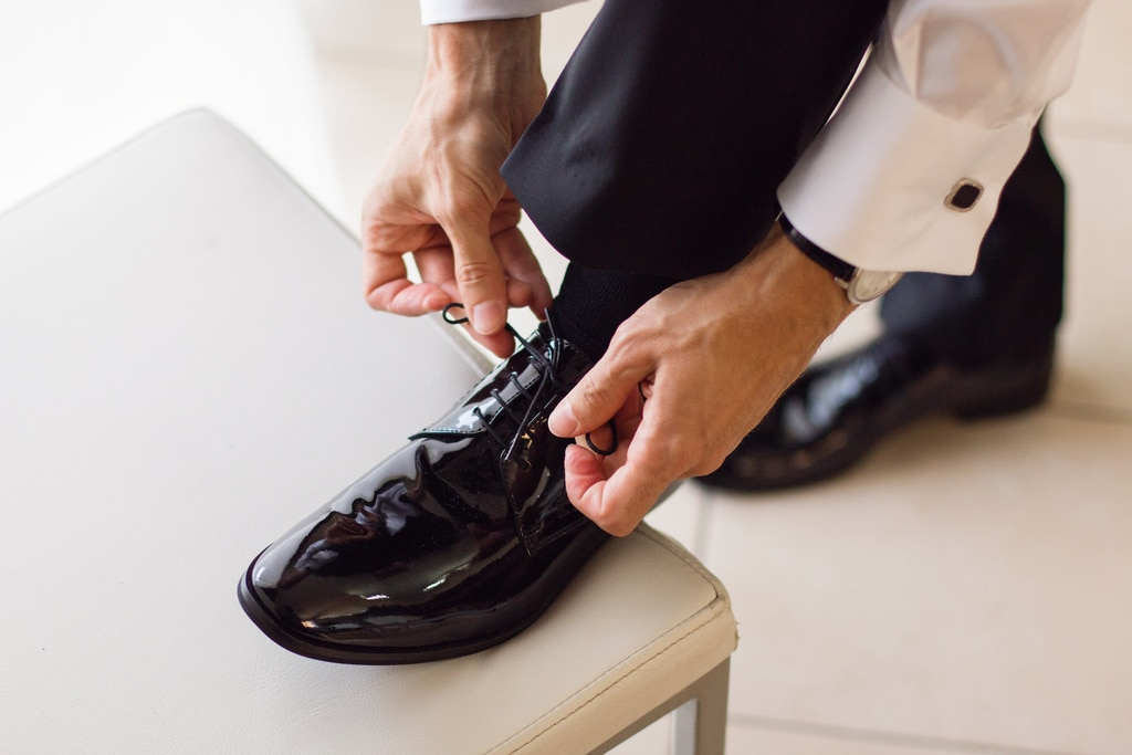 Groom tide his tuxedo shoes on a chair