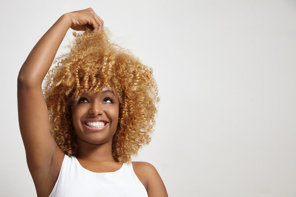 Black woman with curly blond hair