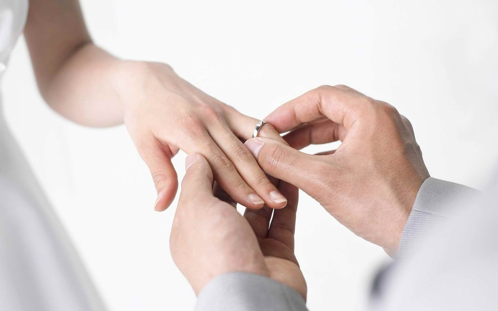 Man putting an engagement ring on fiancée's hand