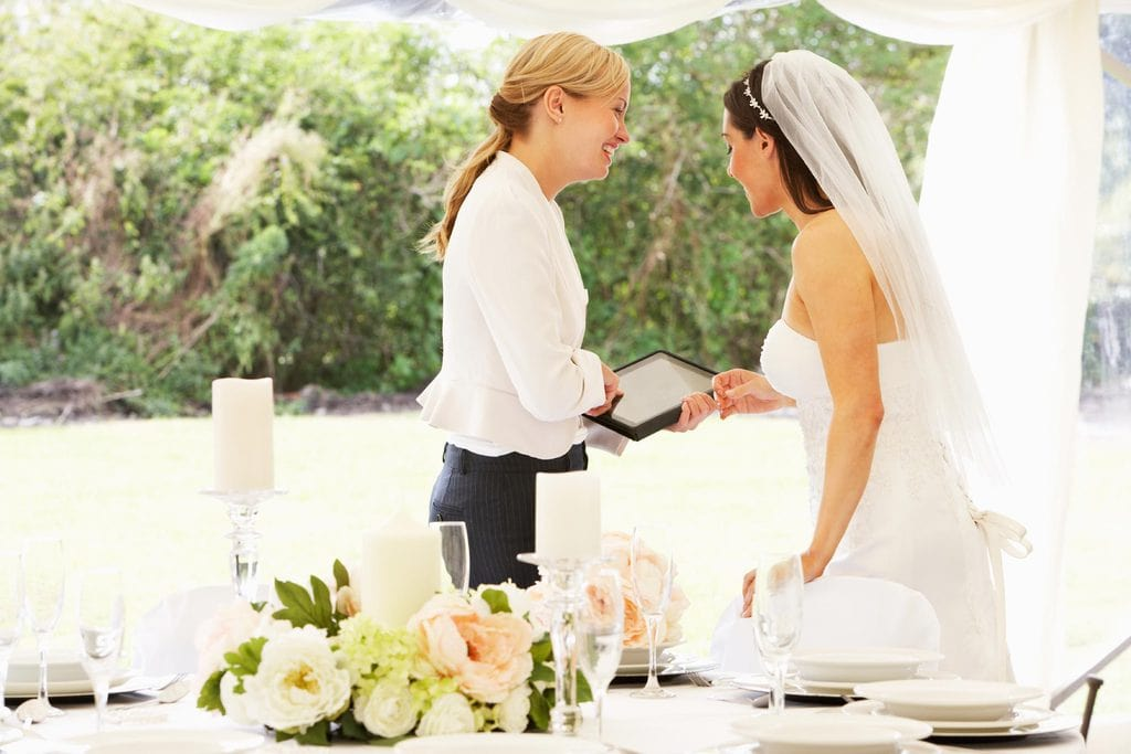 Wedding planner speaking with bride before the reception