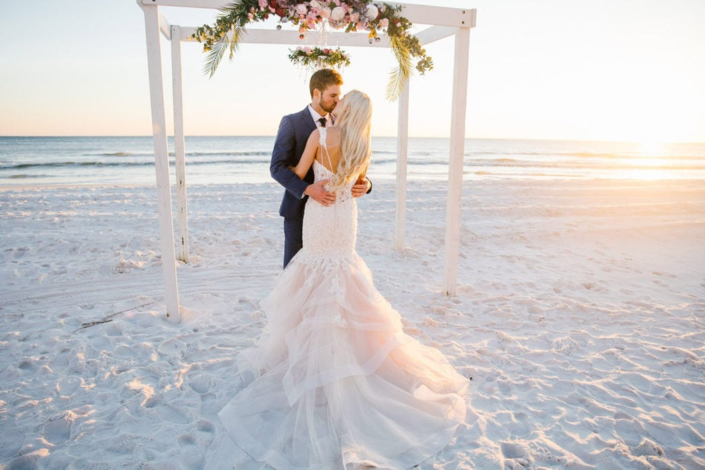 a bride and a groom on the beach