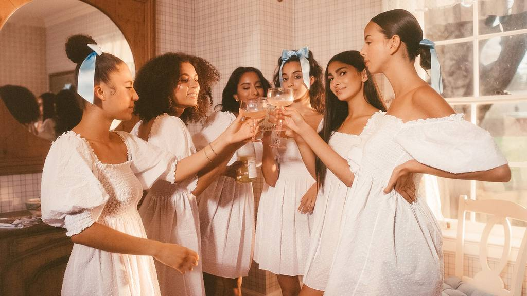 women wearing white clothes drinking