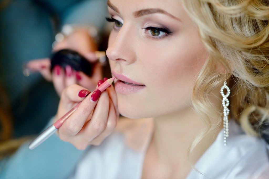 Wedding makeup artist doing the makeup for a bride.